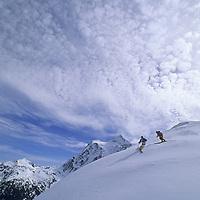 Powder skiers descend Shukson Arm near Mount Baker Ski Area. Mount Shuksan rises in the background.