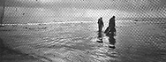 Salmon netters Bob Ritchie (left) and Jim Mitchell head home along the sands after fishing 'jumper' nets at low tide at Kinnaber, Angus.<br /> Ref. Catching the Tide 35/00/36 (30th May 2000)<br /> <br /> The once-thriving Scottish salmon netting industry fell into decline in the 1970s and 1980s when the numbers of fish caught reduced due to environmental and economic reasons. In 2016, a three-year ban was imposed by the Scottish Government on the advice of scientists to try to boost dwindling stocks which anglers and conservationists blamed on netsmen.