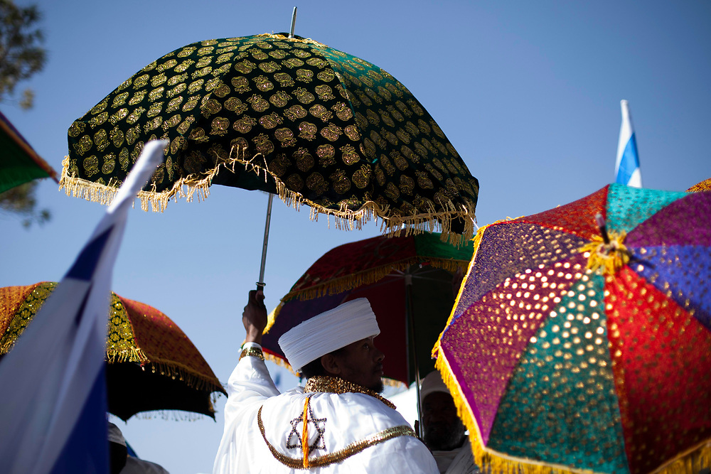 """A member of the Ethiopian Jewish community holds an umbrella as """"Kessim"""", religious leaders of the community pray during a ceremony marking the Ethiopian Jewish holiday of Sigd in Jerusalem, on November 04, 2010. The holiday symbolizes the community's desire for """"return to Jerusalem""""."""