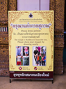 """03 APRIL 2015 - CHIANG MAI, CHIANG MAI, THAILAND:  A sign at the entrance to the """"wiharn"""" (prayer hall) at Wat Ou Sai Kham in Chiang Mai asks visitors to dress and behave appropriately when they visit a Buddhist temple. Thailand has had problems with visitors who dress immodestly or behave improperly in temples, desecrating the holy places.     PHOTO BY JACK KURTZ"""
