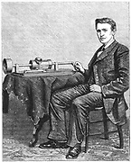 Thomas Alva Edison (1847-1931) American inventor, with early hand-driven model of his phonograph. Engraving published 1878