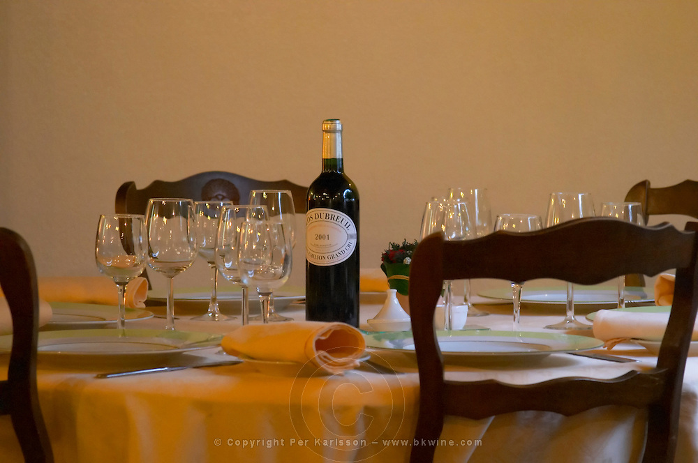 In the restaurant at the Hotel de France in Branne a table laid with table ware, plates, glasses of varying sizes serviettes and a bottle of Chateau du Breuil Saint Emilion Grand Cru 2001 Entre-deux-Mers Bordeaux Gironde Aquitaine France