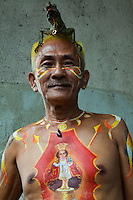 """Man with his Iguana and body painting of Santo Nino the local patron saint of Cebu. Santo Nino is typically clothed in expensive textile robes mostly donations from fervent devotees in the Philippines and abroad. Santo Nino is """"big"""" in Cebu City, though with no known connections to iguanas."""