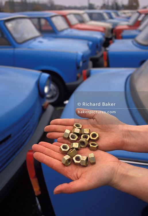 "Six months after the fall of the Berlin Wall, a pair of hands cup some nuts that go towards the construction of Trabant cars at the car factory in the former East Germany (DDR) where the last Trabants await buyers outside the factory production line, on 1st June 1990, in Zwickau, eastern Germany (former DDR). The DDR-produced Trabant suffered poor performance, but its smoky two-stroke engine regarded with affection as a symbol of the more positive sides of East Germany. Many East Germans streamed into West Berlin and West Germany in their Trabants after the opening of the Berlin Wall. It was in production without any significant change for nearly 30 years. The name Trabant means ""fellow traveler"" in German."