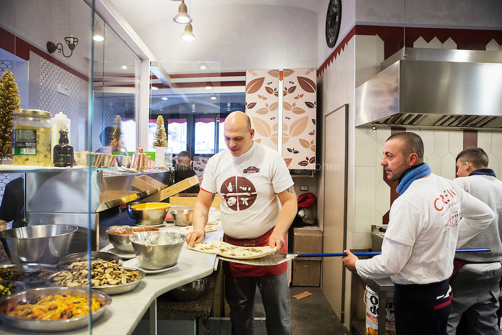 """NAPLES, ITALY - 12 DECEMBER 2014: Pizza makers are about to oven cook a pizza at the Pizzeria Oliva da Concettina ai Tre Santi (where customers can offer """"suspended pizzas""""), in the Sanità district in Naples, Italy, on December 12th 2014.<br /> <br /> The suspended pizzas derives from the tradition of the caffè sospeso,or suspended coffee. The suspended coffee is a cup of coffee paid for in advance as an anonymous act of charity. The tradition began in the working-class cafés of Naples, where someone would order a sospeso, paying the price of two coffees but receiving and consuming only one. A poor person enquiring later whether there was a sospeso available would then be served a coffee for free."""