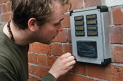 Man speaking into door intercom,