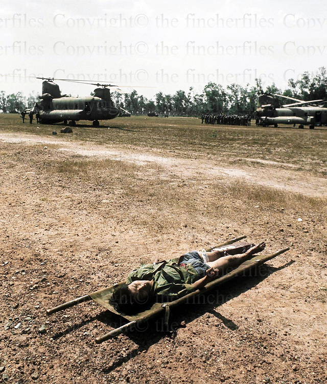 Dead South Vietnamese soldier still on a stretcher during the evacuation of Xuan Loc as the North Vietnamese army approaches. April 1975. Photographed by Terry Fincher