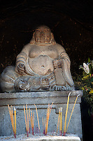 Happy Buddha with offerings of incense at A-Ma Temple in Macau.