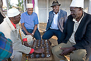 Elderly Muslim men sitting around the market in Iringa, Tanzania, playing a game called Bao. Bao has many names all over the world but is probably best known as Mancala. This version of the game originates from Zanzibar.