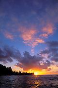 Pink clouds and silhouetted peaks at sunset over Tunnels Beach, Na Pali Coast, Island of Kauai, Hawaii USA
