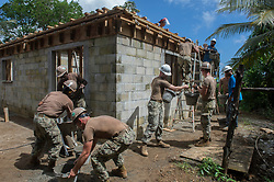 KOSRAE, Micronesia (May 17, 2017) Sailors assigned to Naval Mobile Construction Battalion (NMCB) 1 work with Kosraean workers to construct the Walung Health Clinic in Kosrae, Micronesia. NMCB-1 provides expeditionary construction and engineering support to expeditionary bases and responds to humanitarian assistance disaster relief requests. (U.S. Navy Combat Camera photo by Information Systems Technician 1st Class Ledget Glover III/Released)170517-N-YV613-0290<br />