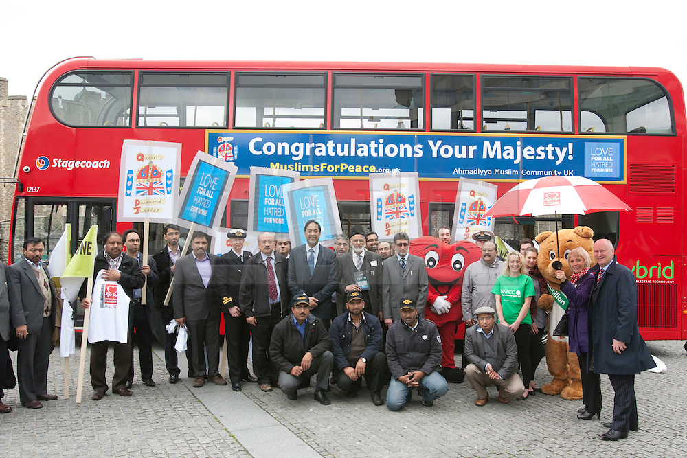 "© licensed to London News Pictures. London, UK 10/05/2012. Supporters of Diamond Jubilee posing next to a bus with has a banner reading ""Congratulations Your Majesty!"" outside Tower of London, today (10/05/12). Ahmadiyya Muslim Association and various charities launching a campaign to celebrate the Queen's Diamond Jubilee. The campaign will have 100 London buses with banners reading ""Congratulations Your Majesty!"" and a charity walk on this Sunday. Photo credit: Tolga Akmen/LNP"