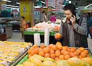 Young Chinese man using cellphone whilst choosing oranges in supermarket, Chongqing, China