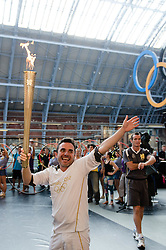 © Licensed to London News Pictures. 26/07/2012. London, UK.  London 2012 Olympics - the Olympic Torch at on its penultimate day (Day 69) of the Olympic Torch Relay at St Pancras International rail station .  Luke Corduner hands the torch over to Danny McCubbin.  Danny takes the torch and waves to the crowd.  Photo credit : Richard Isaac/LNP