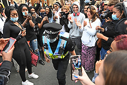 © Licensed to London News Pictures. 09/06/2020. Oxford, UK. A police officer takes a knee for the crowd as Campaigners gather at Oriel College at Oxford University, where they are calling for the removal of a statue of controversial imperialist Cecil Rhodes. Black Lives Matter protesters recently pulled down a statue of slave trader Edward Colston in Bristol town centre, following the death of George Floyd in the U. S. A . Photo credit: Ben Cawthra/LNP