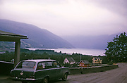Vauxhall Victor estate car with GB registration by roadside, Røldal village and Røldalsvatnet fjord in background, Vestland, Norway in 1970