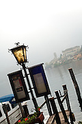 Lantern and the island monastery of Isola San Giulio from the harbor of Orta San Giulio, Piedmont, Italy.
