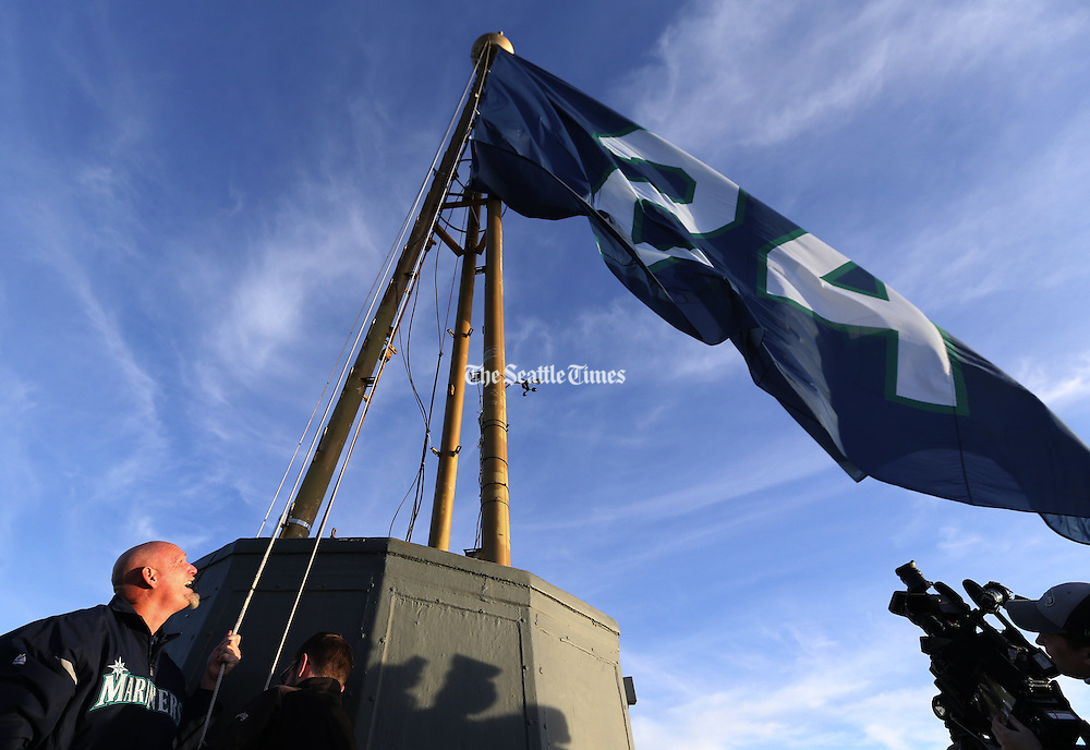 Mariners great Jay Buhner raises a No. 24 flag atop the Space Needle against a blue Seattle sky in honor of teammate Ken Griffey Jr.'s election Wednesday to the National Baseball Hall of Fame. <br /> <br /> Ken Lambert / The Seattle Times