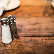 Salt and pepper shakers on a table made of reclaimed wood.