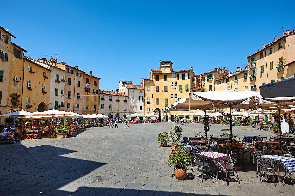 Terrace cafe's in the Piazza dell'Anfiteatro inside the ancinet Roman ampitheatre of Lucca, Tunscany, Italy . Piazza dell'Anfiteatro is a public square in the northeast quadrant of walled center of Lucca. The ring of buildings surrounding the square, follows the elliptical shape of the former second century Roman amphitheater of Lucca. The square can be reached through four gateways located at the four vertices of the ellipse. A cross is carved into the central tile of the square with the arms pointing to the four gateways of the square. The base of the former amphitheater  dating back to the 1st or 2nd century BC, at its peak had about 18 rows of amphitheater seats held some 10,000 spectators.<br /> <br /> Visit our ITALY HISTORIC PLACES PHOTO COLLECTION for more   photos of Italy to download or buy as prints https://funkystock.photoshelter.com/gallery-collection/2b-Pictures-Images-of-Italy-Photos-of-Italian-Historic-Landmark-Sites/C0000qxA2zGFjd_k<br /> .<br /> <br /> Visit our ROMAN ART & HISTORIC SITES PHOTO COLLECTIONS for more photos to download or buy as wall art prints https://funkystock.photoshelter.com/gallery-collection/The-Romans-Art-Artefacts-Antiquities-Historic-Sites-Pictures-Images/C0000r2uLJJo9_s0 If you prefer to buy from our ALAMY PHOTO LIBRARY  Collection visit : https://www.alamy.com/portfolio/paul-williams-funkystock/lucca.html .