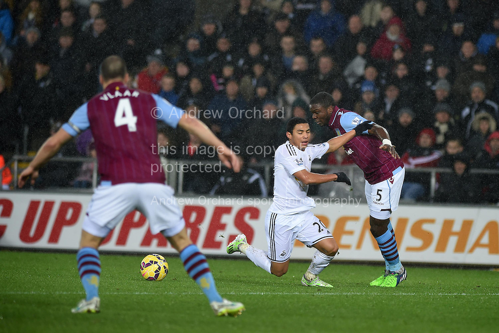 Jefferson Montero of Swansea city © is fouled by Jores Okore of Aston Villa (5) for which a free kick is awarded and Swansea's Gylfi Sigurdsson scores from it. Barclays Premier league match, Swansea city v Aston Villa at the Liberty stadium in Swansea, South Wales on Boxing Day, Friday 26th December 2014<br /> pic by Andrew Orchard, Andrew Orchard sports photography.