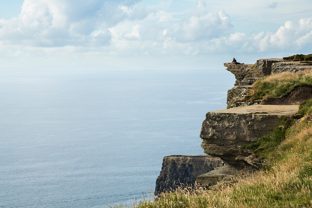 Visitors atop overhanging precipice at the Cliffs of Moher
