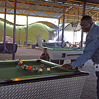 Africa, Namibia, Windhoek. Pool tables at the back of the open-air market in Windhoek provide amusement for the local men.