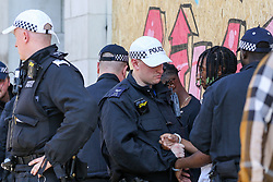© Licensed to London News Pictures. 25/08/2019. London, UK.Police officers carries out stop and search during the family day of the 2019 Notting Hill Carnival. Thousands of revellers take part in Notting Hill Carnival, Europe's largest street party and a celebration of Caribbean traditions and the capital's cultural diversity. Photo credit: Dinendra Haria/LNP