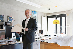 Portrait of a senior architect showing architectural model and standing in the office, Freiburg im Breisgau, Baden-Wuerttemberg, Germany