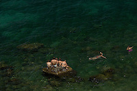 An aerial view of a group of young swimmers in the sea off of the island of Capri, Italy.