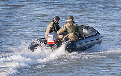 © Licensed to London News Pictures. 12/02/2018. London, UK. Members of a Royal Navy Bomb Disposal Team arrive by boat near London City Airport which remains closed after a World War II era bomb was found in The River Thames during routine work on nearby King V Dock. Police have evacuated nearby residents, closed the airport and set up a 214-metre exclusion zone. Photo credit: Peter Macdiarmid/LNP
