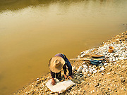 "01 APRIL 2016 - WANG NUEA, LAMPANG, THAILAND:  A man gets ready to pan for gold in the Mae Wang. Villagers in the Wang Nuea district of Lampang province found gold in the Mae Wang (Wang River) in 2011 after excavation crews dug out sand for a construction project. A subsequent Thai government survey of the river showed ""a fair amount of gold ore,"" but not enough gold to justify commercial mining. Now every year when the river level drops farmers from the district come to the river to pan for gold. Some have been able to add to their family income by 2,000 to 3,000 Baht (about $65 to $100 US) every month. The gold miners work the river bed starting in mid-February and finish up by mid-May depending on the weather. They stop panning when the river level rises from the rains. This year the Thai government is predicting a serious drought which may allow miners to work longer into the summer. The 2016 drought has lowered the water level so much that the river is dry in most places and people can only pan for gold in a very short stretch of the river.     PHOTO BY JACK KURTZ"