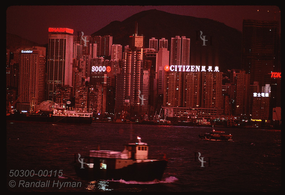 Glass skyscrapers reflect glow of evening sky as boats cruise harbor; view of HK from Kowloon. Hong Kong