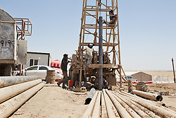 © Licensed to London News Pictures. 27/07/2014. Erbil, Iraq. Workmen drill well to provide drinking water for Iraqi refugees at a camp for internally displaced persons (IDP's) at the Kalak Checkpoint near Erbil in Iraqi-Kurdistan. © Licensed to London News Pictures.