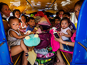 23 JANUARY 2018 - CAMALIG, ALBAY, PHILIPPINES: People in the back of a Jeepney in Camalig wait to be taken to an evacuation center. They live near the Mayon volcano and were evacuated because of the volcano's eruption. The Mayon volcano continued to erupt Tuesday, although it was not as active as it was Monday. There were ash falls in communities near the volcano. This is the most active the volcano has been since 2009. Schools in the vicinity of the volcano have been closed and people living in areas affected by ash falls are encouraged to stay indoors, wear a mask and not participate in strenuous activities.    PHOTO BY JACK KURTZ