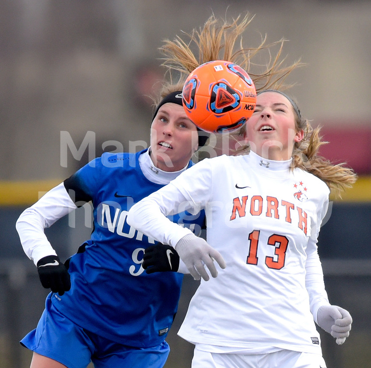 Wheaton North's Jaden Trometer (9) and Naperville North's Hannah Martin (13) head the the ball during girls soccer in Naperville on Wednesday, April 4, 2018.