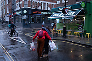 On a rainy night in Soho, three friends hug on Dean Street during the coronavirus pandemic, on 27th August 2020, in London, England.