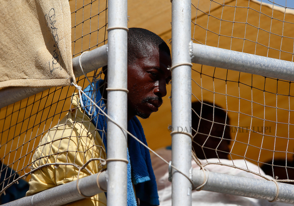 Sub-Saharan migrants sit on the deck of the Migrant Offshore Aid Station (MOAS) ship MV Phoenix in Vibo Valentia, Italy, July 31, 2015.  195 migrants who were rescued off Libya on Wednesday arrived in Italy on Friday afternoon. The Phoenix, manned by personnel from international non-governmental organisations Medecins san Frontiere (MSF) and MOAS, is the first privately funded vessel to operate in the Mediterranean.<br /> REUTERS/Darrin Zammit Lupi <br /> MALTA OUT. NO COMMERCIAL OR EDITORIAL SALES IN MALTA
