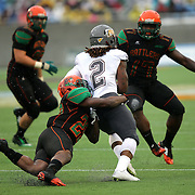 Quarterback Larry Brihm (2) is tackled by Florida A&M Rattlers defensive back Peter Tulloch (29) during the Florida Classic NCAA football game between the FAMU Rattlers and the Bethune Cookman Wildcats at the Florida Citrus bowl on Saturday, November 22, 2014 in Orlando, Florida. (AP Photo/Alex Menendez)