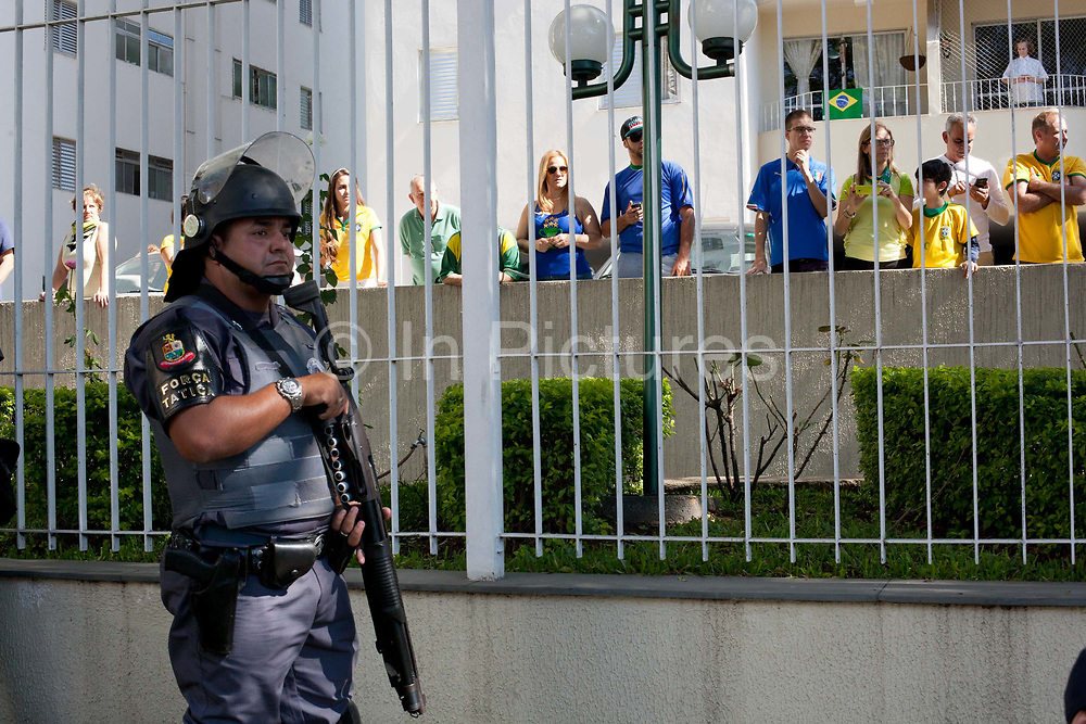 Members of the public residents of the blocks cheer the Police whilst they clash with several hundred protesters in Sao Paulo, Brazil, using tear gas and stun grenades on the opening day of the FIFA World Cup 2014. There were some arrests and injuries inlcuding a CNN producer. The protesters were dispearsed relatively quickly due to the Brazilian Police's early show of force.