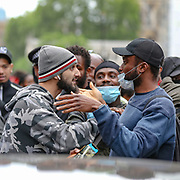 Protestors interact with one-another near Downing Street during a demonstration in Parliament Square in London on Wednesday, June 3, 2020, over the death of George Floyd, a black man who died after being restrained by Minneapolis police officers on May 25. Protests have taken place across America and internationally after a white Minneapolis police officer pressed his knee against Floyd's neck while the handcuffed black man called out that he couldn't breathe. The officer, Derek Chauvin, has been fired and charged with murder. (Photo/ Vudi Xhymshiti)