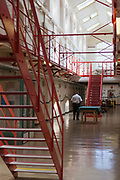 A prison officer walks through D wing, one of the residential wings at HMP Kingston. Kingston prison is a category C prison holding indeterminate sentenced prisoners. Portsmouth, United Kingdom.