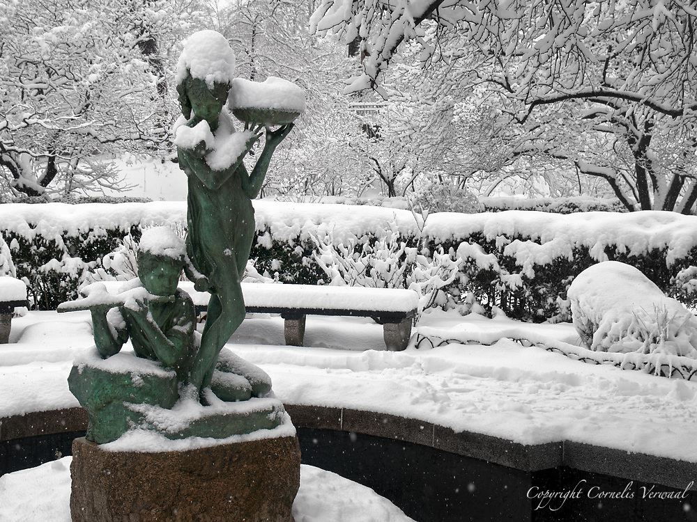 Fountain at the Central Park Conservatory Garden during a snow storm. It is a memorial tribute to Frances Hodgson Burnett, author of the children's classics The Secret Garden and Little Lord Fauntleroy.