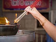 10 JANUARY 2014 - BANGKOK, THAILAND: A person lights incense at Wat Mangkon Kamalawat in the Chinatown section of Bangkok. It is the largest Mahayana (Chinese style) Buddhist temple in Chinatown.        PHOTO BY JACK KURTZ