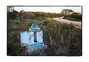 SHOT 2/17/19 5:51:21 PM - A motorcyclist rides past a small and simple capilla in the countryside on the outskirts of the small town of Yaaxhon in the Yucatan in Mexico. The capillas are often dedicated to certain patron saints or in this case someone that has died at or near the site. Often times they contain prayer candles, pictures, personal artifacts or notes. (Photo by Marc Piscotty / © 2019)