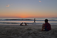 Early morning on a part of China beach in Danang. A young boy wearing the FC Barcelona jersey, is seated on the beah, looking the sun rising on the sea. A man is running along the beach into the water and two kids are playing with sand.