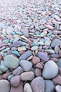 Pebbles in pastel shades of pink, purple, grey and blue, on a beach