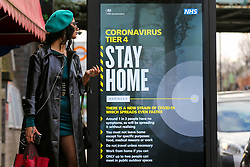 © Licensed to London News Pictures. 25/12/2020. London, UK. A woman looks at the government's 'Stay Home- Tier 4' publicity campaign poster in north London amid fears of a third national lockdown after Christmas as COVID-19 infection rates rise. Many more areas of England will go into Tier 4 restrictions from Boxing Day as the mutated strains continue to spread throughout England. Photo credit: Dinendra Haria/LNP