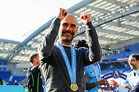 BRIGHTON, ENGLAND - MAY 12:  Manchester City manager Pep Guardiola celebrates in front of the City fans after the Premier League trophy presentation during the Premier League match between Brighton & Hove Albion and Manchester City at American Express Community Stadium on May 12, 2019 in Brighton, United Kingdom. (MB Media)