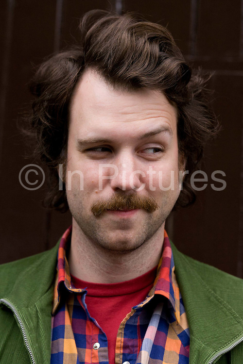 A close-up portrait of a young man in his late-twenties street portrait with moustache. His neatly trimmed mustache is tidy compared to the rather unkempt beard stubble that has formed on his chin.  The young man looks about mid-twenties (20s) and wears a green jacket and checked shirt.